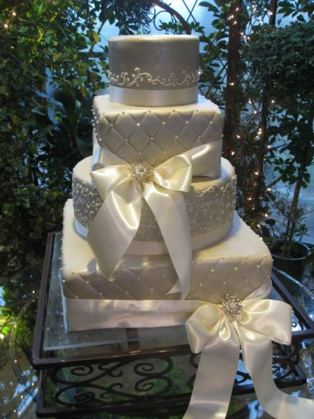 A mix of square and round tiers of cake stacked in the classic wedding cake form. All tiers are covered in white fondant with intricate buttercream detail. White ribbons add elegance and sophistication.
