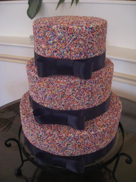 Three tiered cake covered in white buttercream and sprinkles with decorative black ribbon going around each layer.