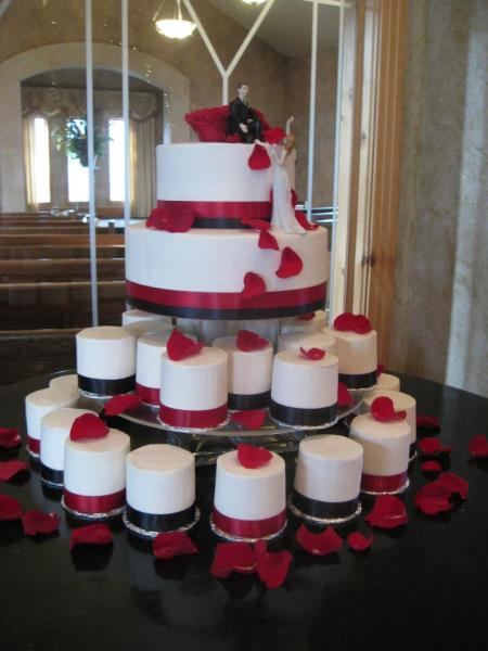 [Image: Two big layers of cake stacked together with many more small layers in the lower levels. All cakes are covered in white fondant with black and red ribbon. The flower petals are all made out of red fondant.  ]