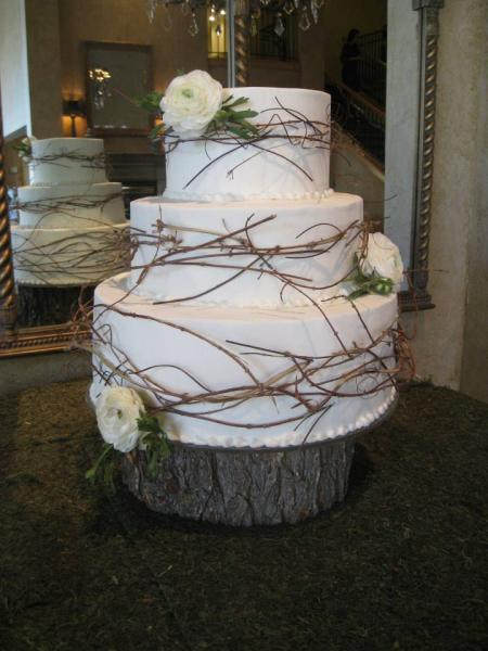 [Image: Three tiered cake covered in white fondant with beaded buttercream detail atop a tree trunk stand. Three white roses, one on each layer of cake, and decorative twigs surround the layers of cake. ]