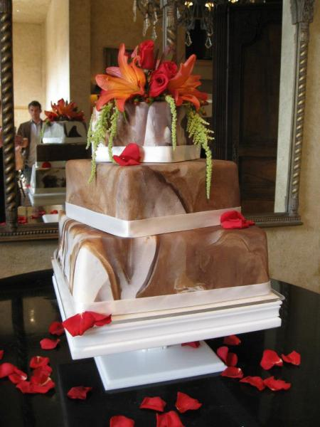 Three square tiers of cake stacked with a beautiful brown and white marble design. Each layer has a white strip of fondant to separate the layers. Flowers in red and orange colors sit on top of the cake for decoration.