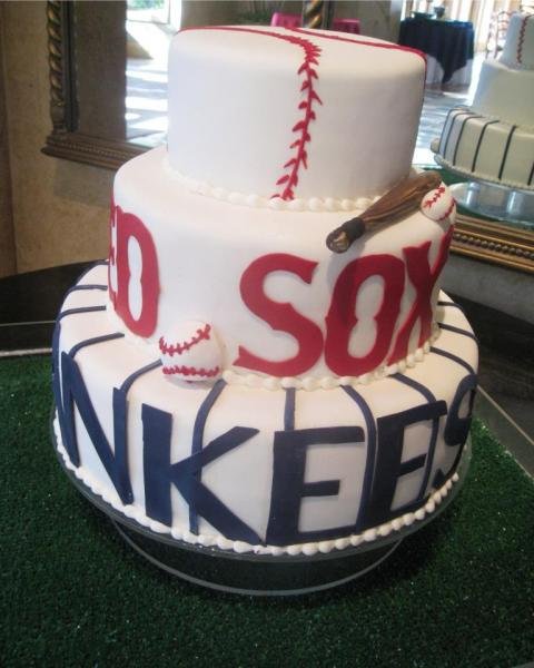 Three layers of cake stacked covered in white fondant with buttercream beaded detail. The design on the first layer, resembling a baseball, is made out of red buttercream. The letters and decorative pieces on the second and third layers are all made out of red and blue fondant.