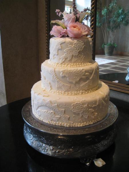 [Image: Three tiered cake covered in white fondant with intricate buttercream design. The cakes sit atop a vintage gray stand and are topped by beautiful pale pink flowers.]