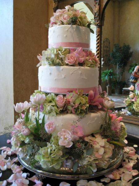 Three tiered cake covered in white fondant with pink ribbon. Decorative flowers in shades of pink and green flood the simple and delicate layers of cake, adding freshness, beauty, and elegance.  This cake is perfect for your spring wedding!