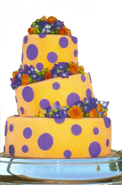 Three tiered crooked polka-dot cake. Orange and purple fondant decorate the cake with blue and orange flowers. Fun, beautiful and unique design!