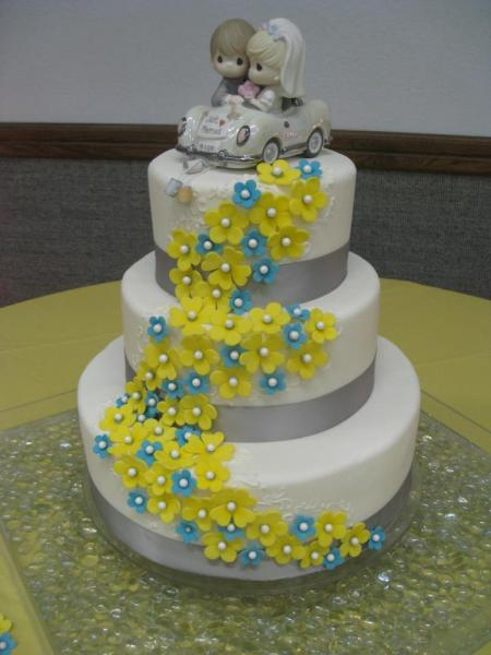 [Image: Three round tears of cake stacked and covered in white fondant. The layers have a gray ribbon going around with small blue and yellow flowers made out of fondant. The cake topper is a cartoon rendition of the bride and groom. ]