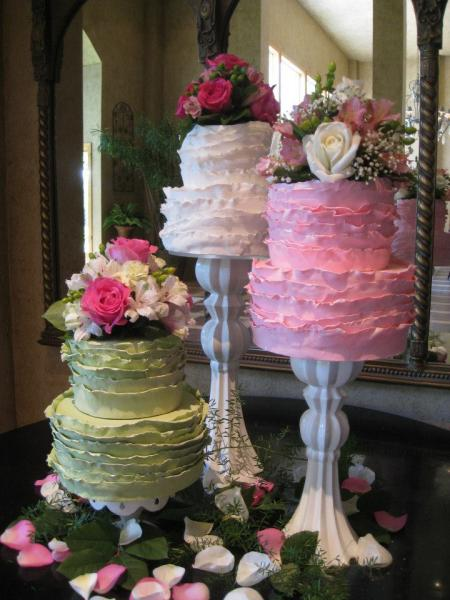 [Image: Three sets of two tiered cakes atop different sized stands. All cakes are covered in white, pink and green buttercream and fondant. Flowers in different soft tones add a fresh look to this wedding cake setup. Beautiful, chic and girly! ]