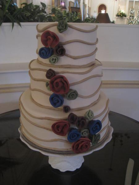 Wedding cake with fondant flowers wedding cakes image beautiful three tiered cake covered in white fondant on top of a white mightylinksfo