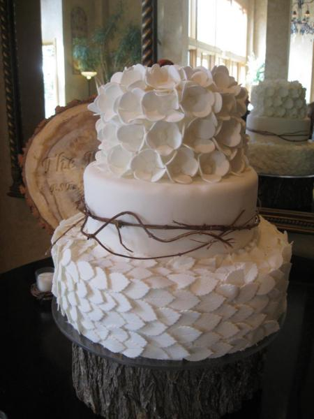 Three tiered wedding cake covered in white fondant seating on top of a tree trunk stand. The first and third layers of cake have flowers and leaves made out of white fondant. The middle layer is wrapped in twigs for a rustic feel.
