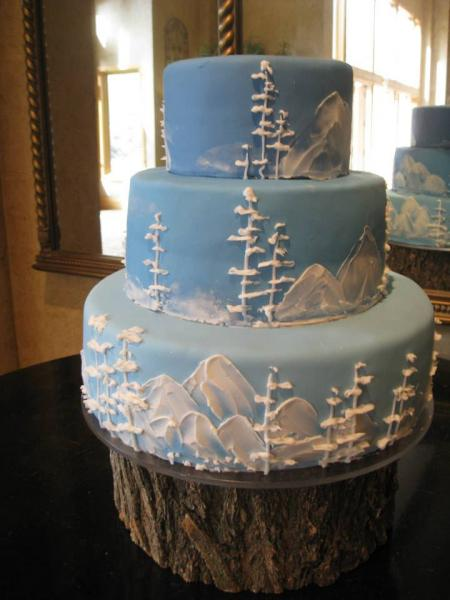 [Image: Three tiered cake covered in light blue fondant atop a tree trunk stand. The trees and mountains have been painted onto the cake using white buttercream in order to create the illusion of ice and snow.]
