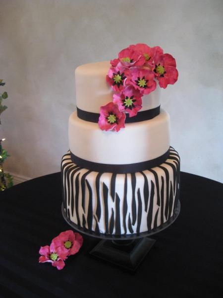 Three tiered cake covered in white fondant. A stripe of black fondant surrounds layers one and two while the third layer of cake shows an amazing zebra-like pattern. Flowers made out of pink fondant add color to this beautiful black and white cake.