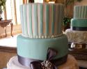 Three tiered cake. The first tier is covered in white fondant with turquoise stripes and buttercream beads. The second layer is covered in turquoise fondant with a navy blue ribbon. The third layer is also covered in fondant with an added layer of buttercream in a flower-like pattern.