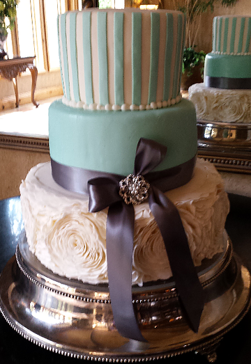 [Image: Three tiered cake. The first tier is covered in white fondant with turquoise stripes and buttercream beads. The second layer is covered in turquoise fondant with a navy blue ribbon. The third layer is also covered in fondant with an added layer of buttercream in a flower-like pattern. ]