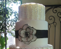 Cake stacked in three tiers. The first and third layers are covered with white buttercream. The second layer is covered with white fondant, a black stripe also made out of fondant and flower.