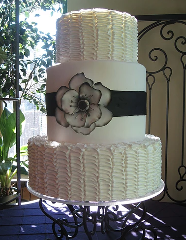 [Image: Cake stacked in three tiers. The first and third layers are covered with white buttercream. The second layer is covered with white fondant, a black stripe also made out of fondant and flower.]