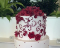 Three tiered cake covered in white buttercream with a maroon ribbon around the second layer. The flowers are made out of maroon fondant. The intricate pattern is a full display of maroon buttercream.