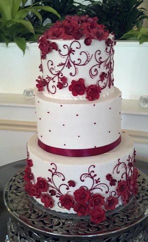 [Image: Three tiered cake covered in white buttercream with a maroon ribbon around the second layer. The flowers are made out of maroon fondant. The intricate pattern is a full display of maroon buttercream.]