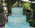 Three tiered cake with golden birds atop a vintage gold stand covered in turquoise fondant. The lovely pattern and beads are made out of white buttercream.