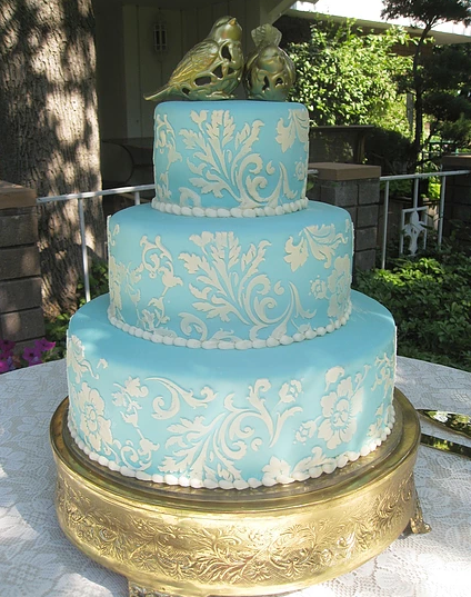 [Image: Three tiered cake with golden birds atop a vintage gold stand covered in turquoise fondant. The lovely pattern and beads are made out of white buttercream. ]