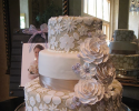 Three tiered cake covered in white and taupe fondant. You can see a flower pattern that resembles lace on the first and third layers. The flowers on the right side are also made out of fondant.