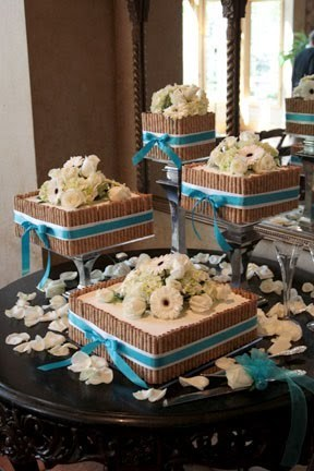 This cake setup for a wedding is definitely different from the classic stacked tiered cake. The layers are square shaped and stand alone to create a different look. They are decorated with edible straws to create a wooden look with white and teal ribbon. Fondant flowers and petals add a perfect touch of countryside beauty!